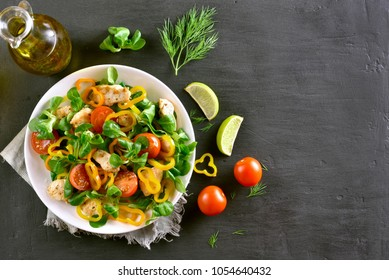 Vegetable salad with chicken meat on dark stone background with copy space. Top view, flat lay