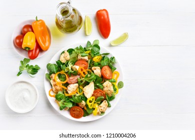 Vegetable salad with chicken meat on white wooden background with copy space. Top view, flat lay