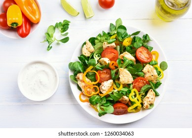 Vegetable salad with chicken meat and sauce on white wooden table. Top view, flat lay