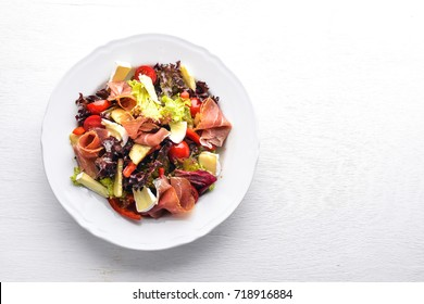 Vegetable salad and diced meat. On a wooden background. Top view. Free space.