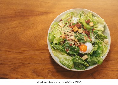 Vegetable salad with egg on wooden table.