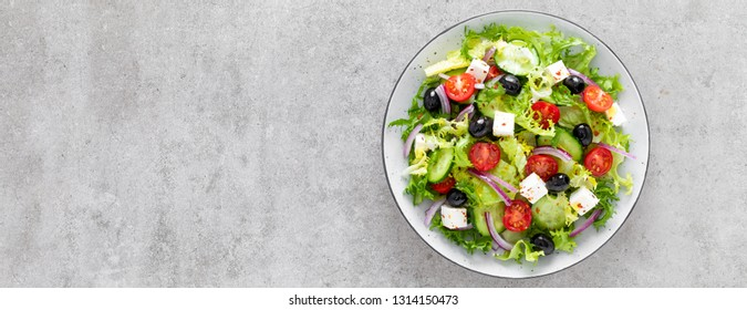 Vegetable salad with fresh cucumber, tomato, olive, onion, lettuce and feta cheese. Healthy food. Top view. Banner