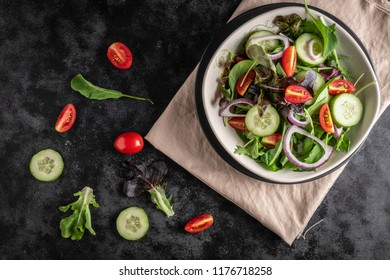 Vegetable salad with fresh lettuce, tomatoes and cucumber in white plate on black background