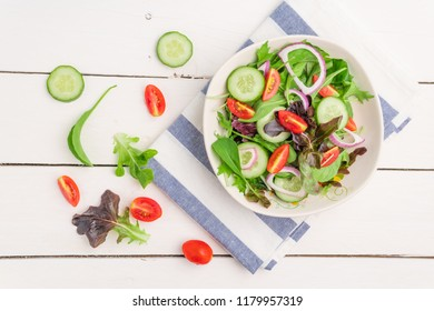 Vegetable salad with fresh lettuce, tomatoes and cucumber in white plate on white table