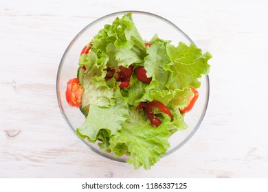 Vegetable salad with fresh lettuce, tomatoes and cucumber in glass bowl. Top view.