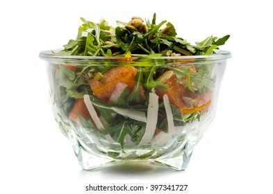 vegetable salad in glass bowl over white