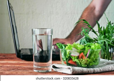 Vegetable salad with a glass of pure water on the wooden table closeup. In the background, a man working with a laptop. The concept of people working outside the office and healthy lifestyle