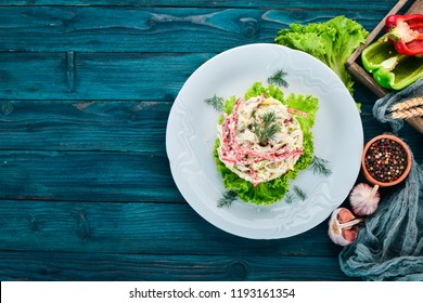 Vegetable salad with mayonnaise. On the old wooden background. Free space for text. Top view.