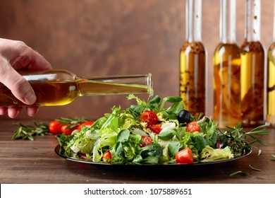 Vegetable salad with olive oil pouring from a small bottle. Old wooden table and brown background. Copy space.
