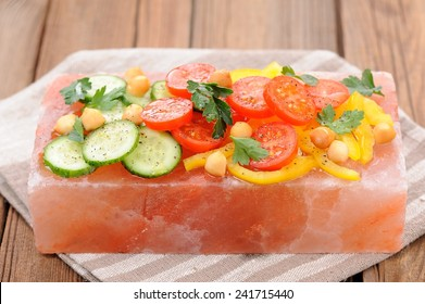 Vegetable salad on pink salt block