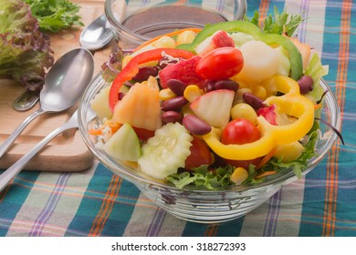 Vegetable salad with oriental salad dressing on stripe table cloth.