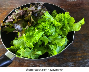 Vegetable salad in a pan on wooden table for food and beverage background.