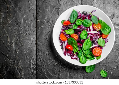 Vegetable salad. Red cabbage, tomato and spinach salad with olive oil. On black rustic background.