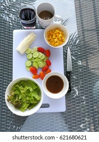 Vegetable Salad with sesame soy sauce dressing, a cup of coffee and grape juice on glass table top.