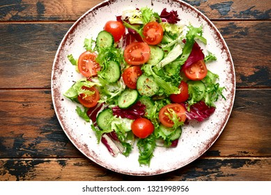 Vegetable salad with tomato and cucumber on a plate over dark wooden background.Top view with copy space.