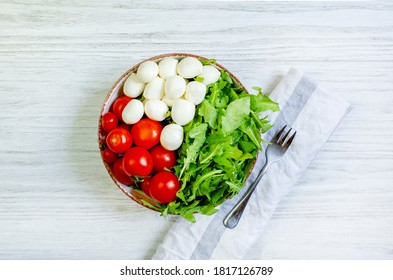 vegetable salad of tomatoes cherry peppers greens arugula mozzarella cheese in a round plate next to a fork on a white wooden table top view