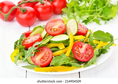 Vegetable salad with tomatoes, cucumbers, bell peppers and rucola