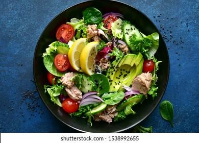 Salade de légumes au thon et à l'avocat sur fond noir sur fond bleu foncé, pierre ou béton. Vue de dessus avec espace de copie.