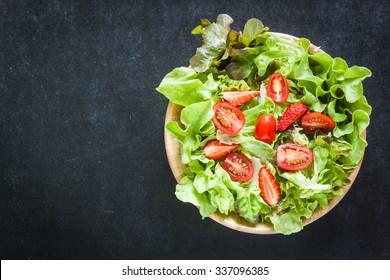 Vegetable salad in wooden bowl on blackboard