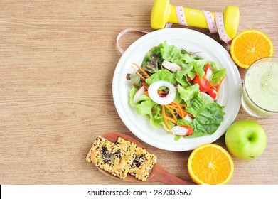 Vegetable salad,cereal cracker,fruits and dumbbell.Health and diet concept