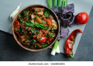 Vegetable saute caponata on a dark background top view.