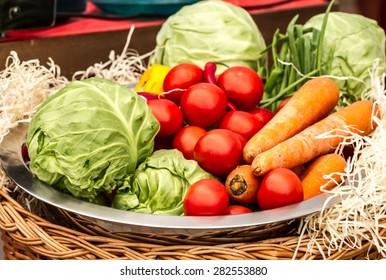 Vegetable set of fresh cabbage, carrots, tomatoes, green onions and red peppers in metal plate