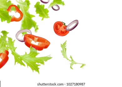 Vegetable slices isolated on white background. Flying lettuce, tomatoes, and bell peppers (salad ingredients) isolated on white background