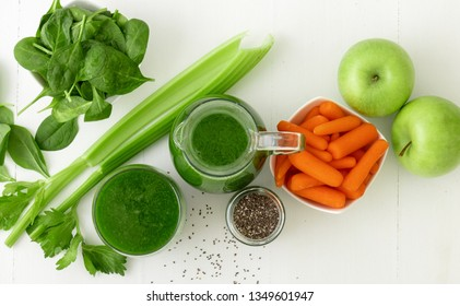 Vegetable smoothie, healthy organic juice made from celery, green apples, leaves of spinach and young carrot. Big pitcher and small glass of green juice, jar with chia seeds. Top view.