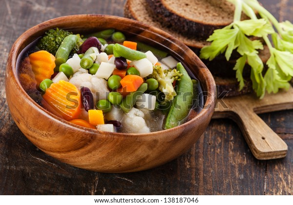 Vegetable soup with bean, pea, carrot and potato in wooden bowl