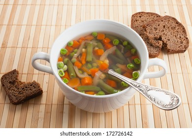 vegetable soup in a bowl with bread on a table