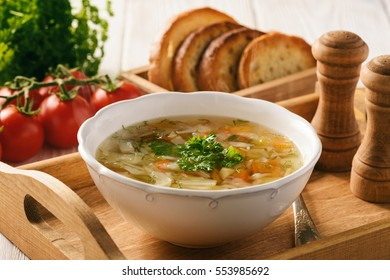 Vegetable soup with bread on wooden tray.