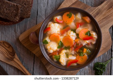 Vegetable soup with cauliflower, carrots and other vegetables on dark background