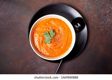 vegetable soup in a ceramic bowl on a brown background. view from above