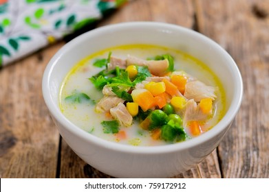 Vegetable soup with corn and peas and chicken. Wooden background