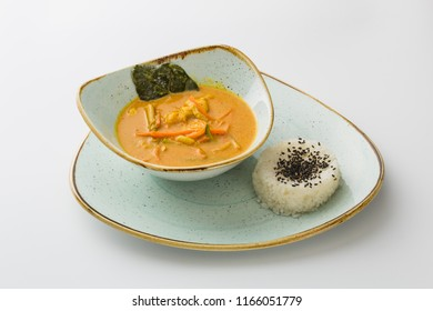 vegetable soup with garnish of rice with flax seeds in a plate isolated on white background.