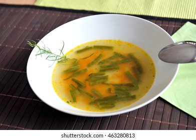 Vegetable soup with green beans in a white plate with spoon.