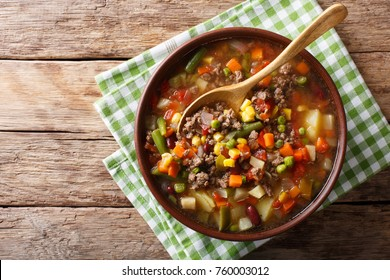 Vegetable soup with ground beef close-up in a bowl on the table. Horizontal top view from above