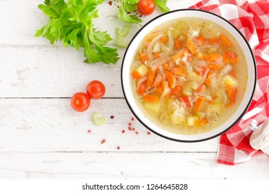 Vegetable soup. Healthy food, vegetarian dish. Vegetable soup with cabbage, potato, tomato, carrot, celery, pepper and green peas. Vegan diet menu. Top view