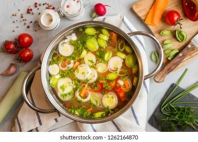 Vegetable soup with leek and parsley in a cooking pot