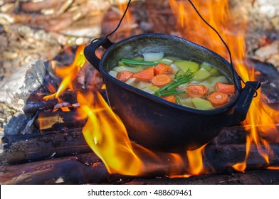 vegetable soup in old tourist pot at fire place Summer trekking activity