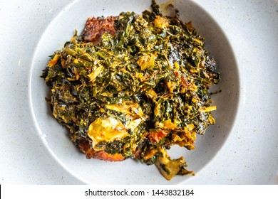 vegetable soup on a white plate. Nigerian food: A bowl of Efo Riro soup. Egusi soup