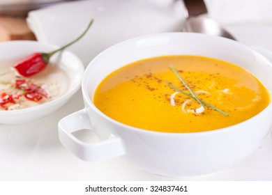 Vegetable soup with pumpkin, carrot, red pepper and cream in white bowl on white background