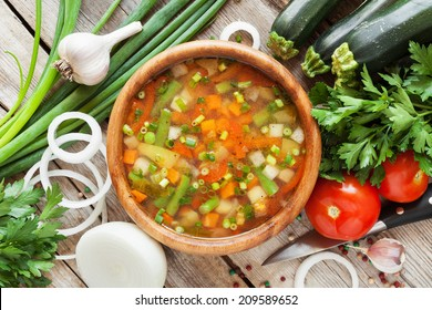 vegetable soup in wooden bowl and ingredients on wooden rustic table. top view