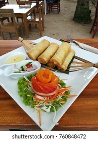 Vegetable spring rolls with decorations side salad with plum sauce.