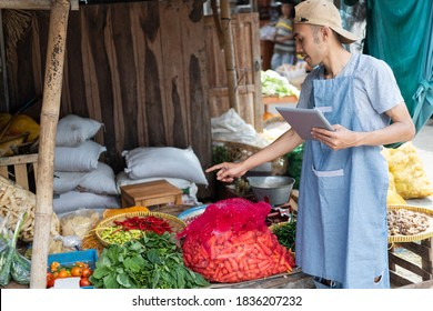vegetable stall man with finger pointing while using the tablet in the vegetable stall background