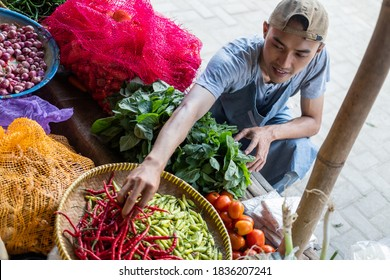 Vegetable stall sales man holding chilies set the display in the background of a traditional vegetable stall