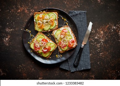 Vegetable toasts. Healthy toasts with cucomber, cherry tomatoes, crumbled feta cheese and radish sprouts on a black plate. Table top view. Dark rusty background.