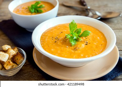 Vegetable tomato and carrot soup with spices, greens and croutons  over rustic wooden background
