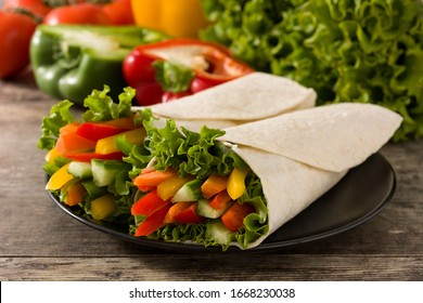 Vegetable tortilla wraps on wooden table