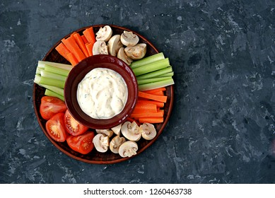 Vegetable tray with a ranch dip on a dark background. Raw vegetable mix includes sliced mushrooms, carrots, celery, tomatoes.